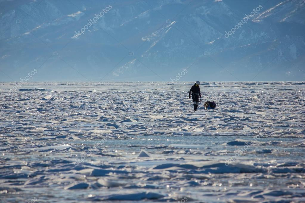 male hiker with backpack walking on ice water surface against peaks on shore,russia, lake baikal