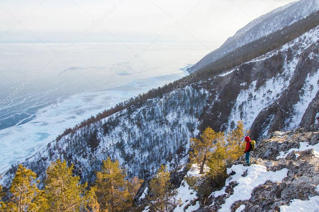 view of mountain slope with snow and trees and standing man,russia, lake baikal
