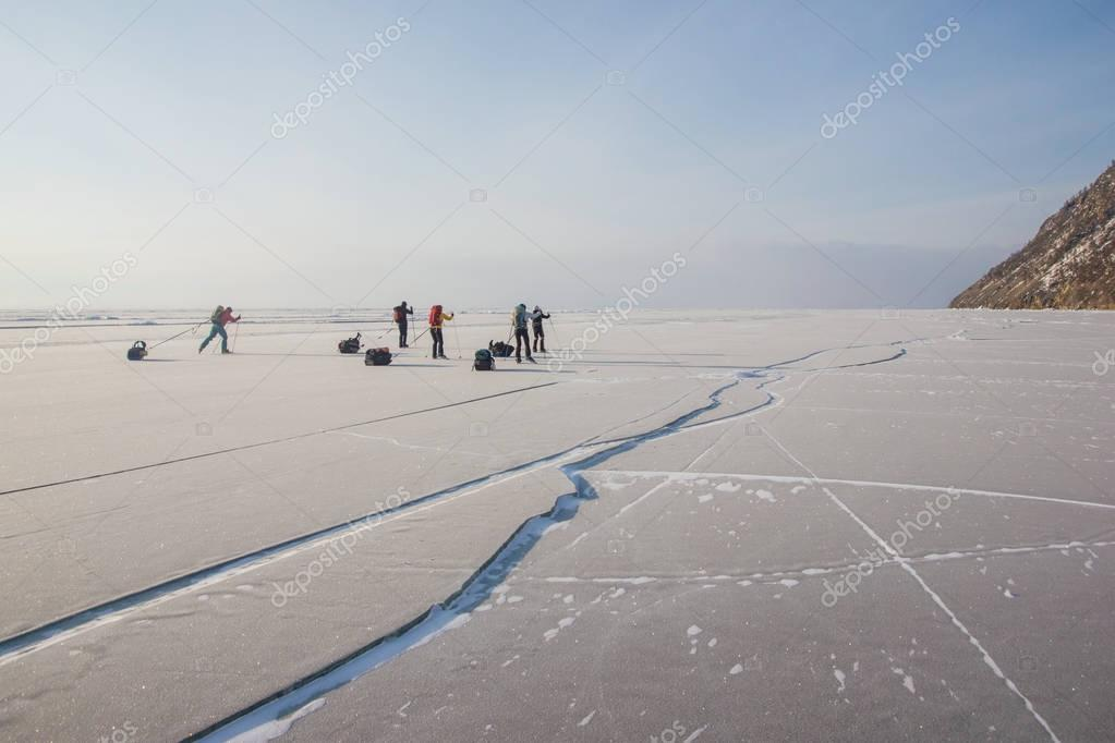 group of tourists walking on ice water surface during daytime, russia, lake baikal