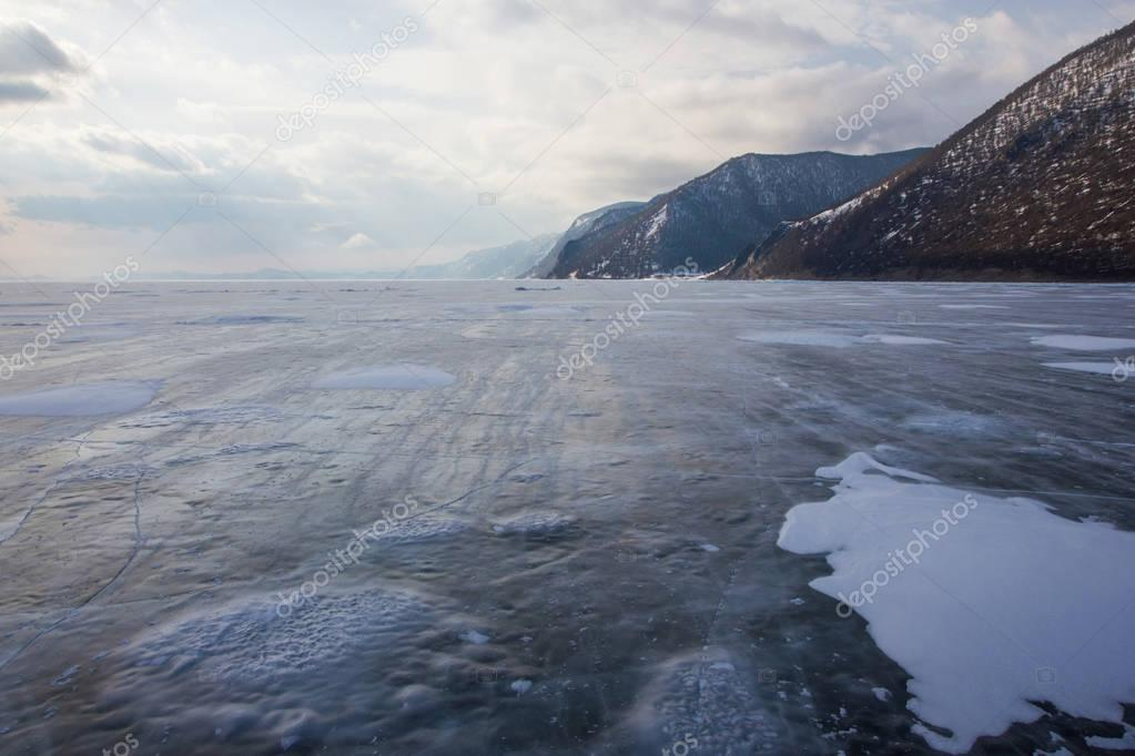 view of lake with ice surface and rocks formations on shore ,russia, lake baikal