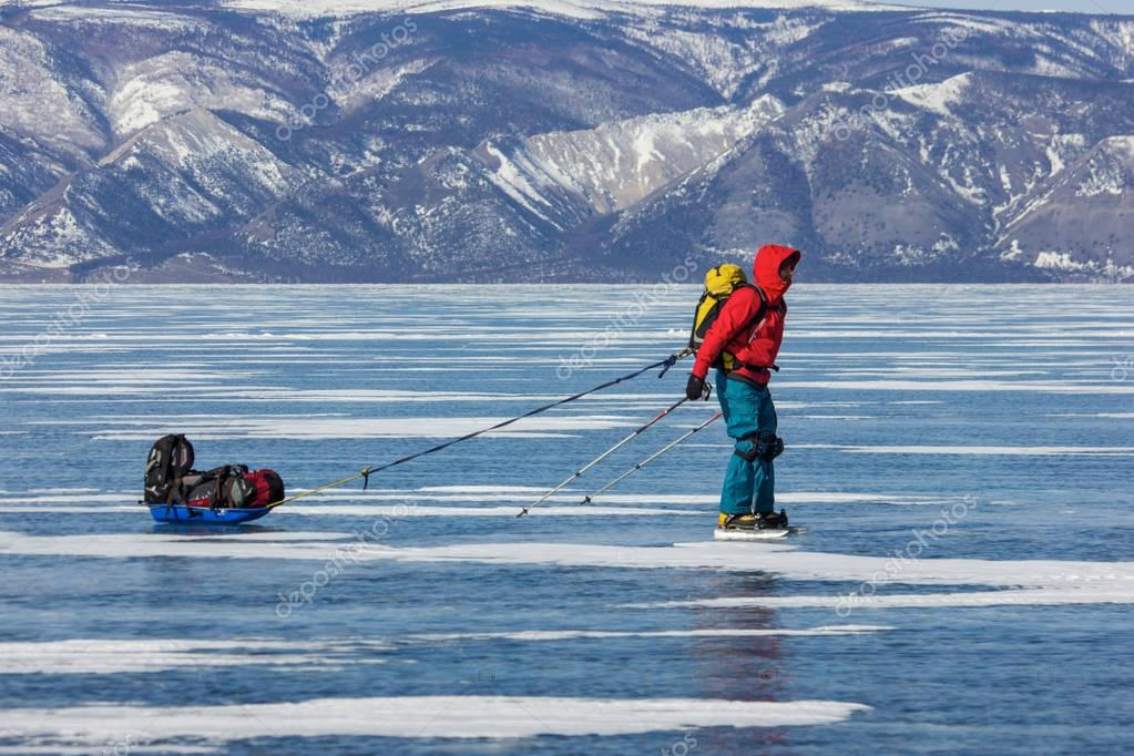 male hiker with backpack standing on ice water surface ,russia, lake baikal
