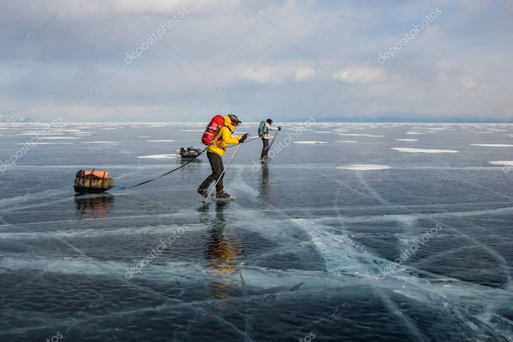 two men with backpacks going through ice water surface and hills on background, Russia, Lake Baikal