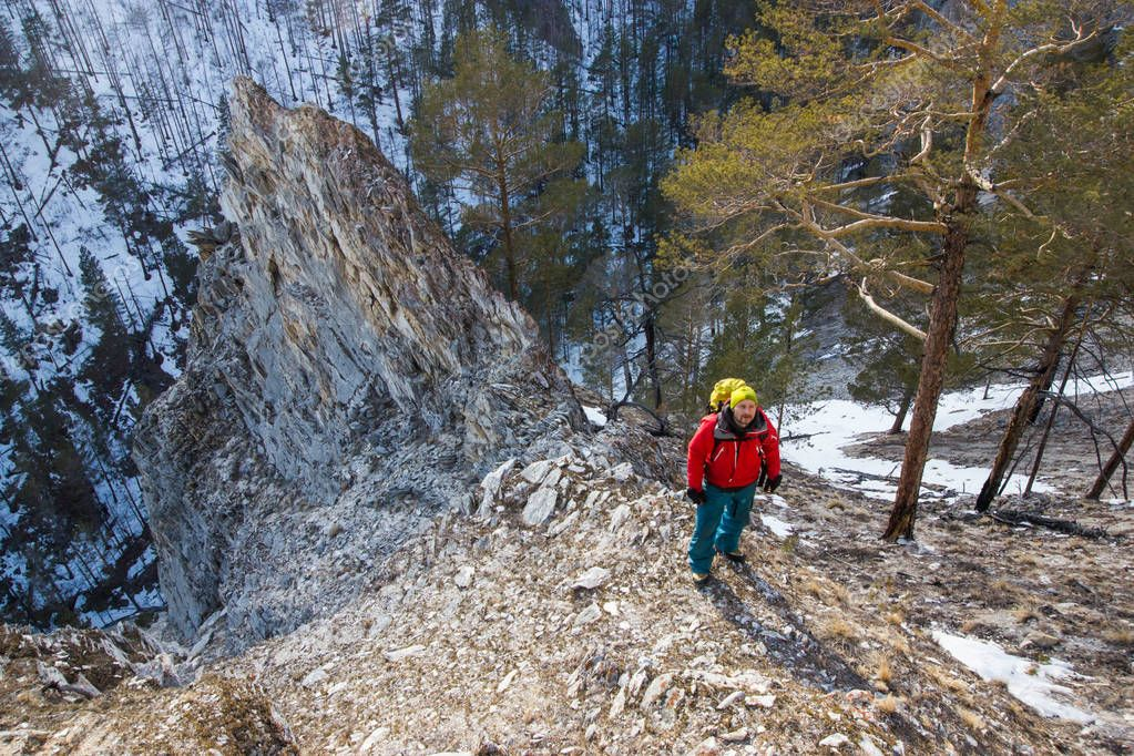 man with backpack stand on slope of rock with trees on foot, Russia, Lake Baikal