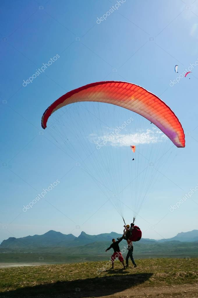 Two men parachuting on field with hills on backgrond, Crimea, Ukraine