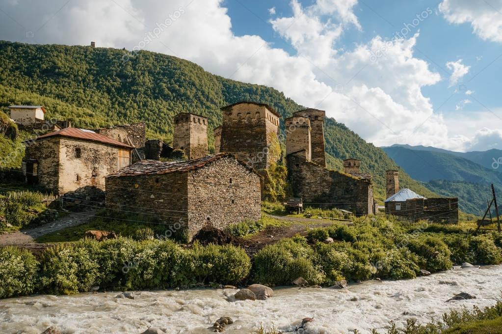 old weathered buildings against small river stream against hills, Ushguli, svaneti, georgia