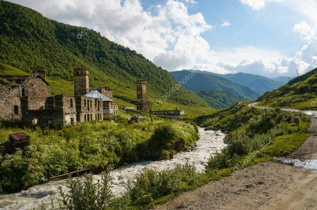 old weathered buildings against small river stream against hills, Ushguli, svaneti, georgia