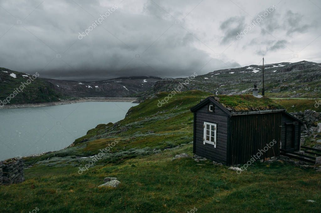rural house over field with green grass against small pond, Norway, Hardangervidda National Park