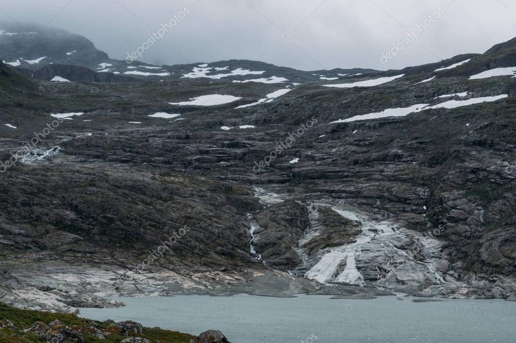 lake on foot of rock with snow on surface, Norway, Hardangervidda National Park