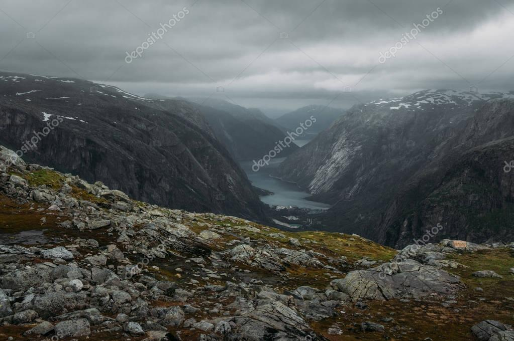 view of slope with stones and rocks and river on foot  on background, Norway, Hardangervidda National Park