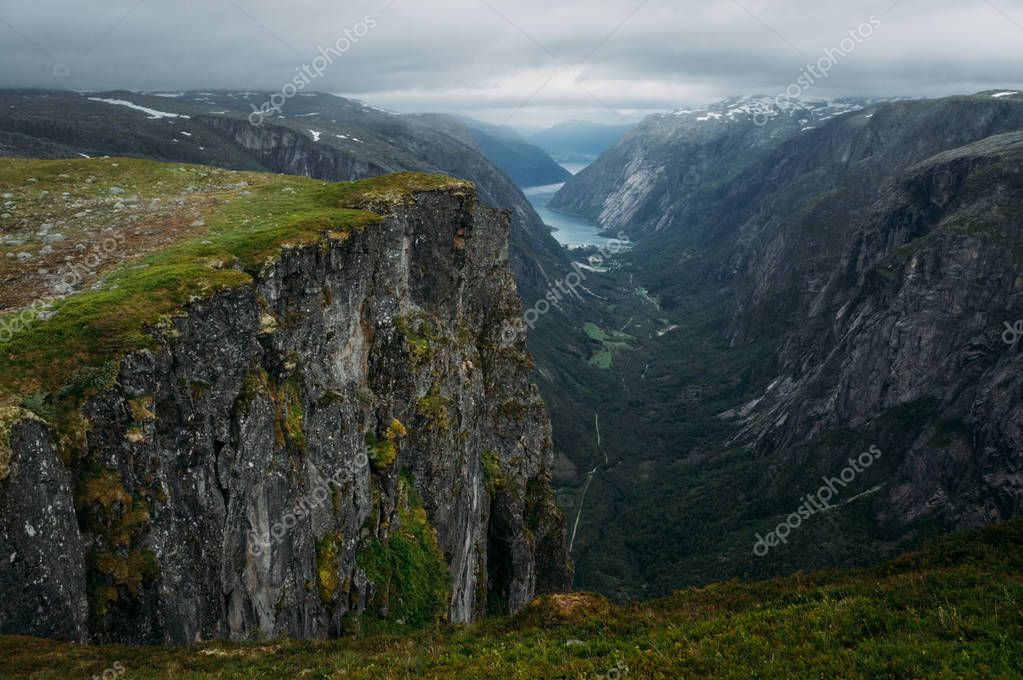 view of rocks and grassy cliff, mountain river on background, Norway, Hardangervidda National Park