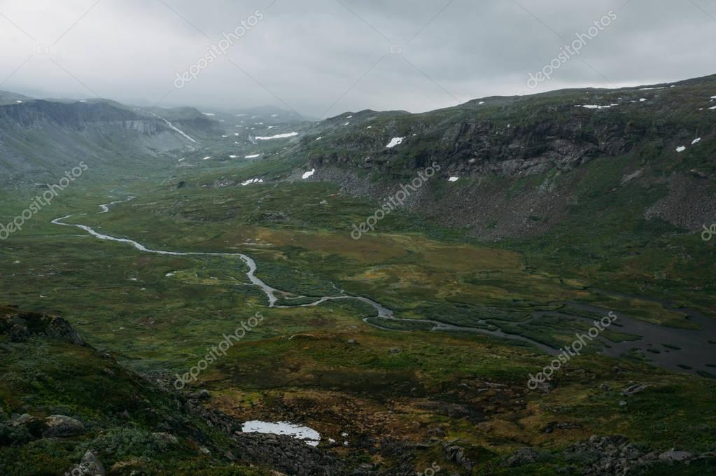 view of green grass field with river stream surrounded by rocky cliffs, Norway, Hardangervidda National Park