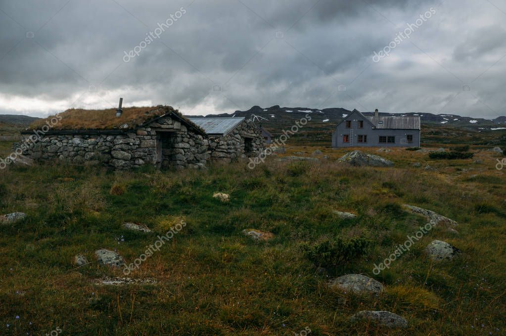 old weathered houses on field with tall grass and stones, Norway, Hardangervidda National Park