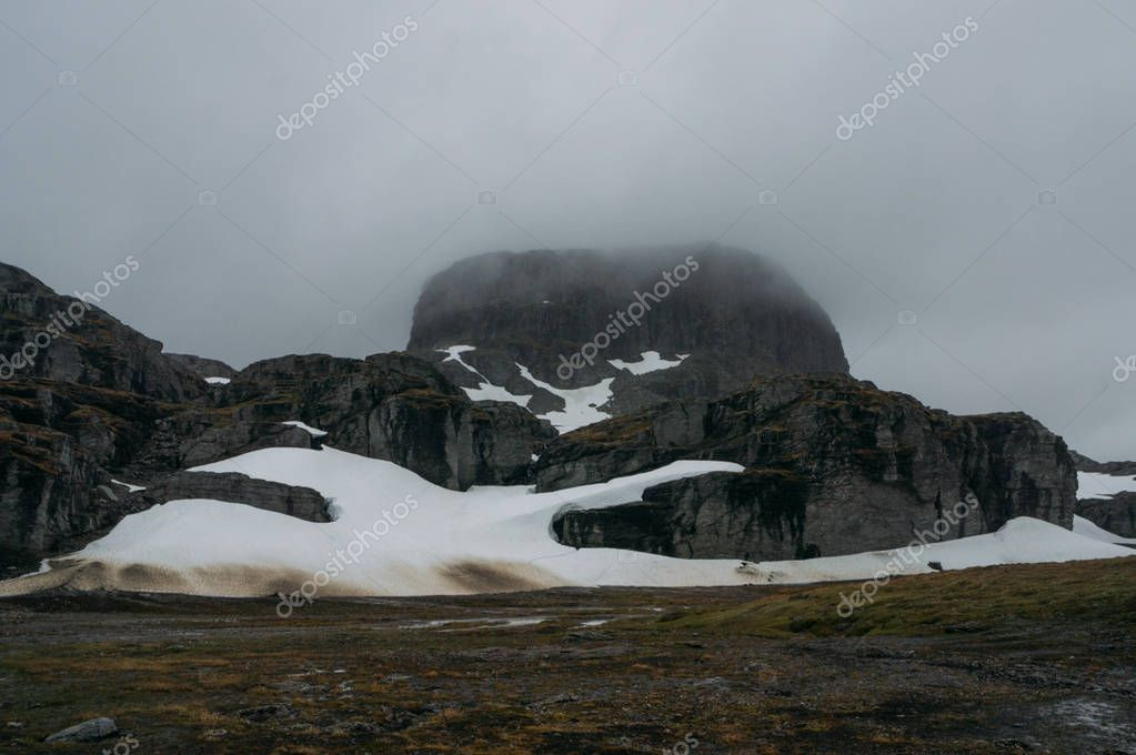 view of rock formation with snow  during foggy weather, Norway, Hardangervidda National Park