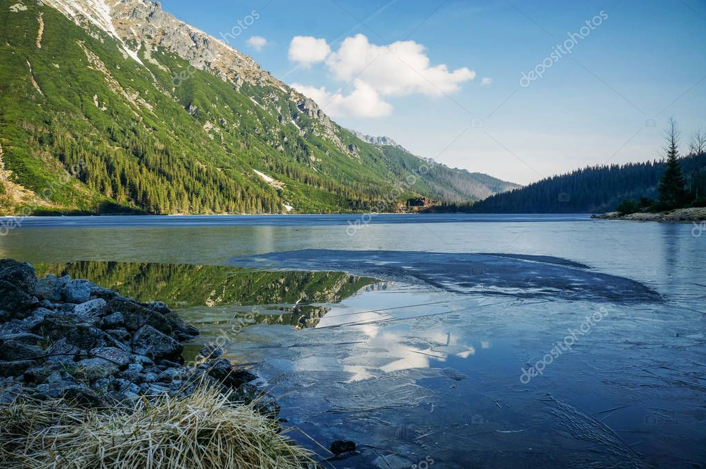 view of mountain lake with trees on slopes of mountain over water, Morskie Oko, Sea Eye, Tatra National Park, Poland