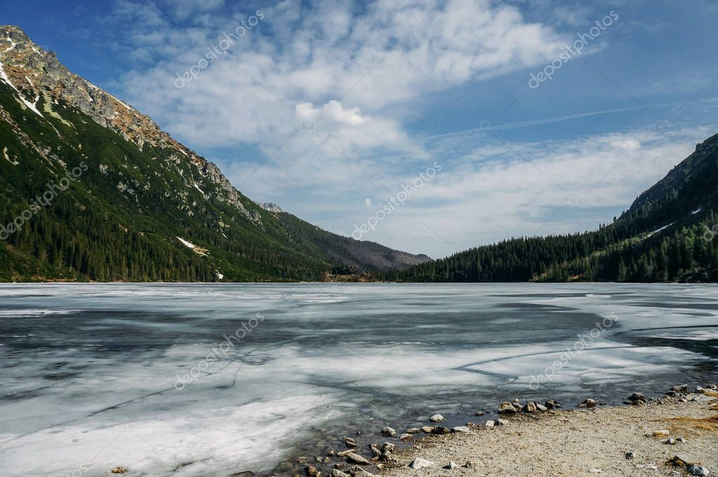 view of lake with ice on surface and mountains on background, Morskie Oko, Sea Eye, Tatra National Park, Poland
