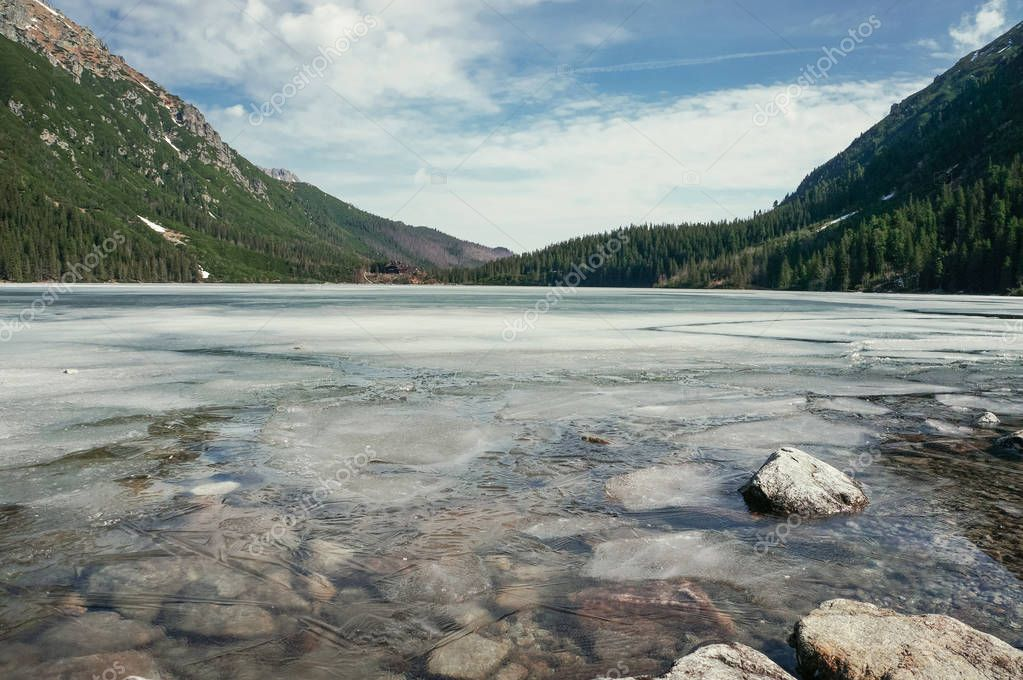 view of stones on water surface on shore with hills on background, Morskie Oko, Sea Eye, Tatra National Park, Poland
