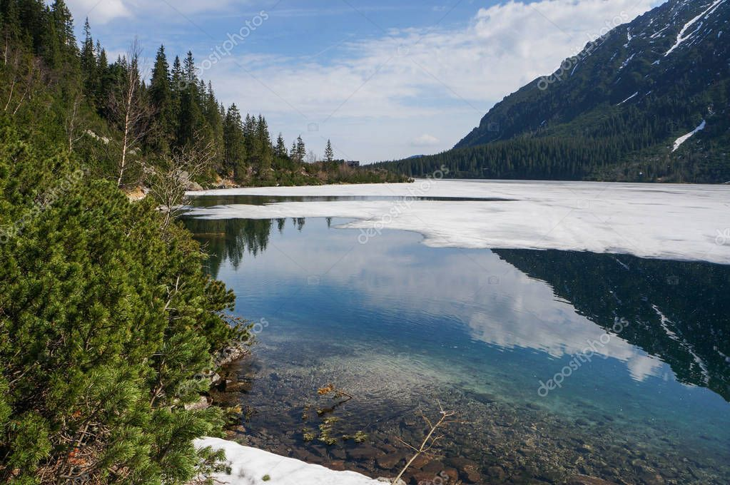 View of mountain lake with ice on surface and mountain hills, Morskie Oko, Sea Eye, Tatra National Park, Poland