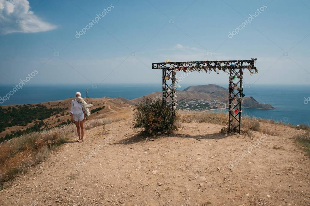 Woman walking in beautiful landscape with decorative arch in Crimean mountains and Black sea, Ukraine, May 2013
