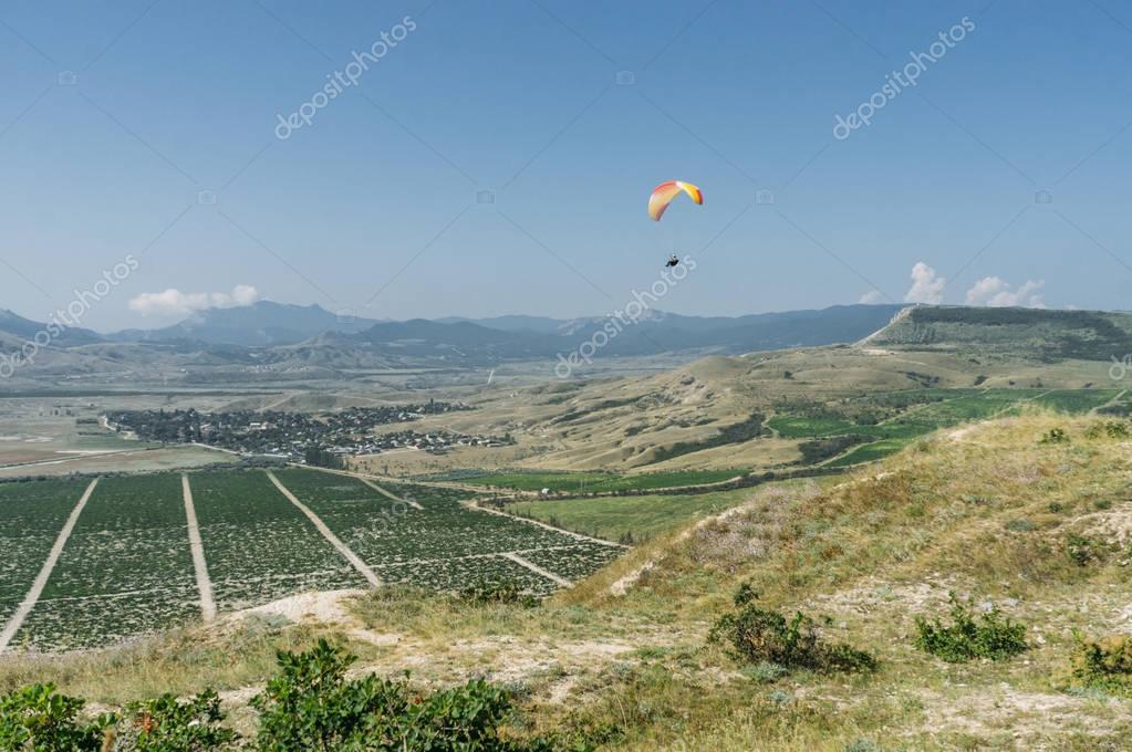Parachutist gliding in blue sky over scenic landscape of Crimea, Ukraine, May 2013