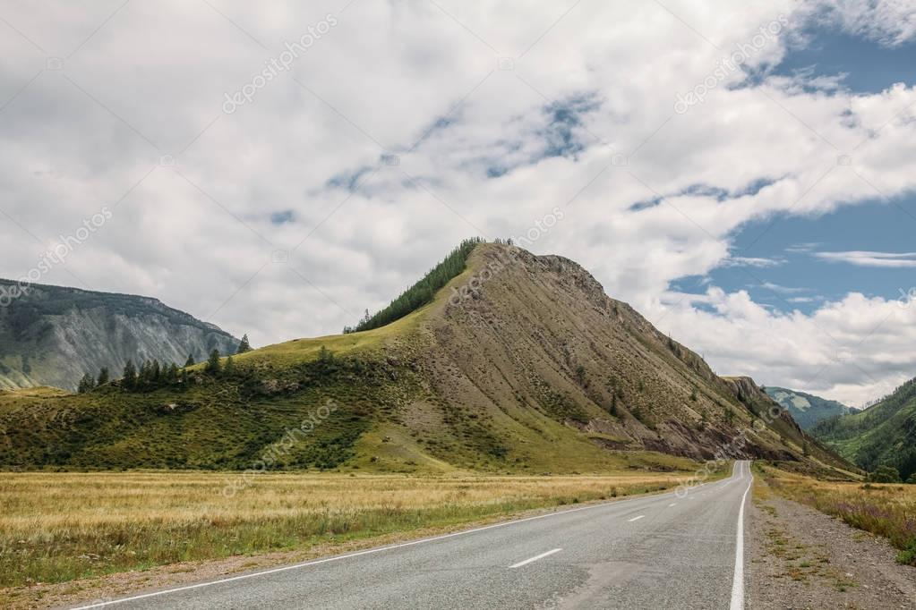 panoramic view of empty road, mountains and cloudy sky, Altai, Russia