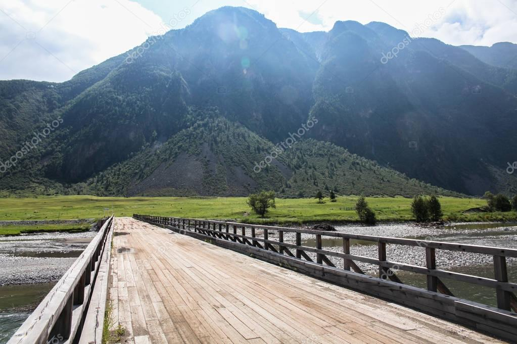 mountain landscape with river and wooden bridge, Altai, Russia