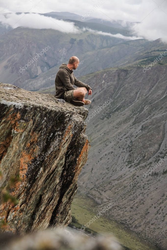young man sitting on cliff and looking beautiful landscape, Altai, Russia