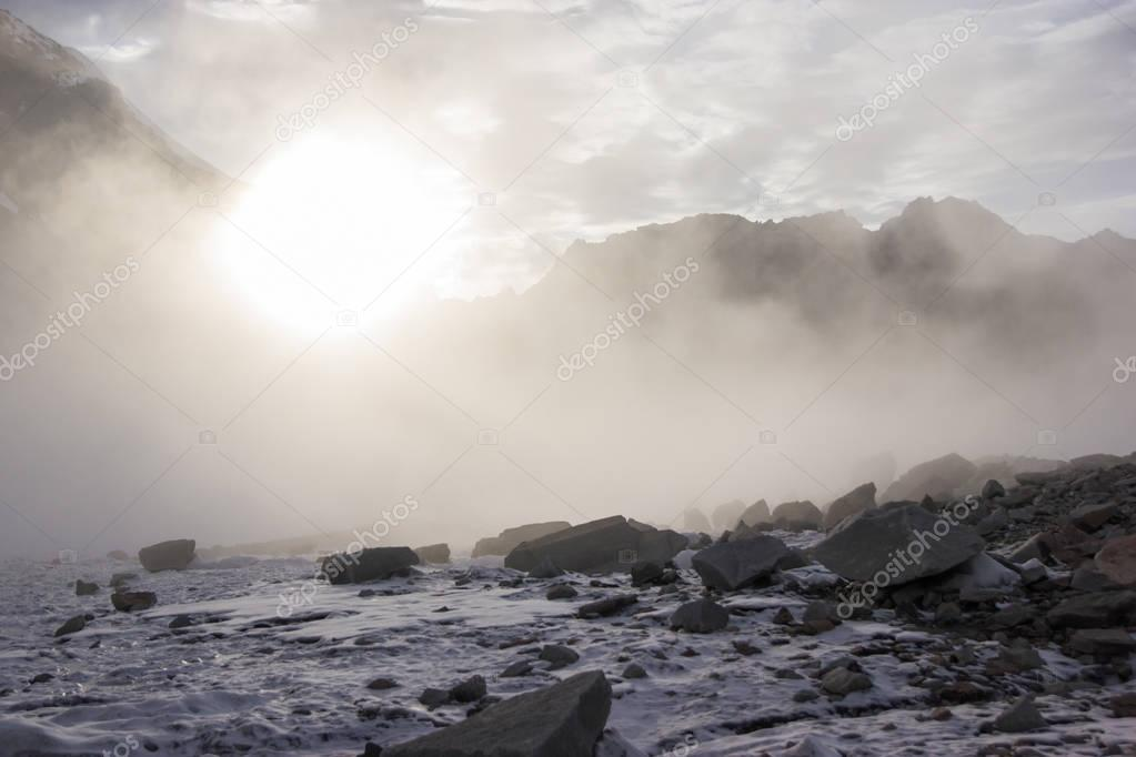snow and rocks in mountains at misty morning, kyrgyzstan, ala archa