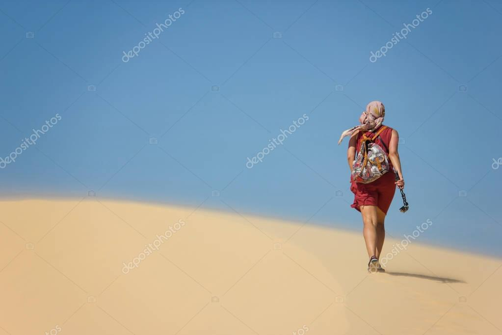 rear view of lonely woman with backpack walking in desert, Vietnam, Phan Thiet