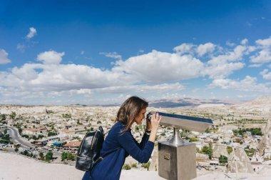 Female tourist looking at city through binocular viewer, Cappadocia, Turkey stock vector