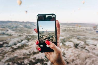 Woman taking photo of Hot air balloons festival on smartphone, Cappadocia, Turkey stock vector