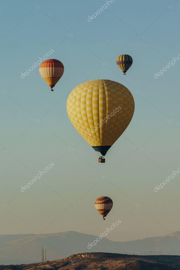 Hot air balloons festival in blue sky in Goreme national park, fairy chimneys, Cappadocia, Turkey