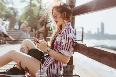 beautiful young woman using smartphone while sitting on pier at beach