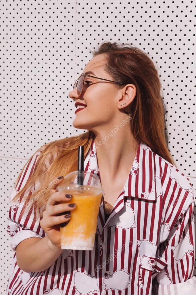 sensual woman with plastic cup of refreshing cocktail leaning back on white wall