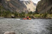 side view of people on kayaks rafting on mountain river and beautiful landscape, Altai, Russia