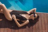 Fotografie pohled z vysokého úhlu krásné mladé ženy v černých plavkách, ležící u bazénu
