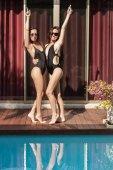 Fényképek vonzó fiatal nők wihle átfogó, a medence melletti felfelé mutató fürdőruhák