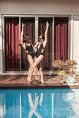 Fényképek boldog, fiatal nők fürdőruhás tánc medence