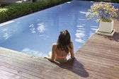 rear view of attractive young woman in pink bikini sitting on edge of pool