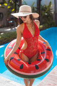 beautiful young woman in swimsuit with watermelon inflatable ring at poolside