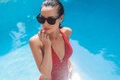 Fotografie pohled z vysokého úhlu smyslná mladá žena v plavkách u bazénu