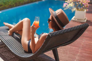 stylish young woman in bikini lying in sun lounge at poolside