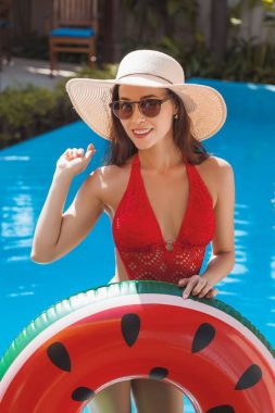 happy young woman in swimsuit with inflatable ring at poolside