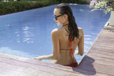 sensual young woman in bikini at swimming pool