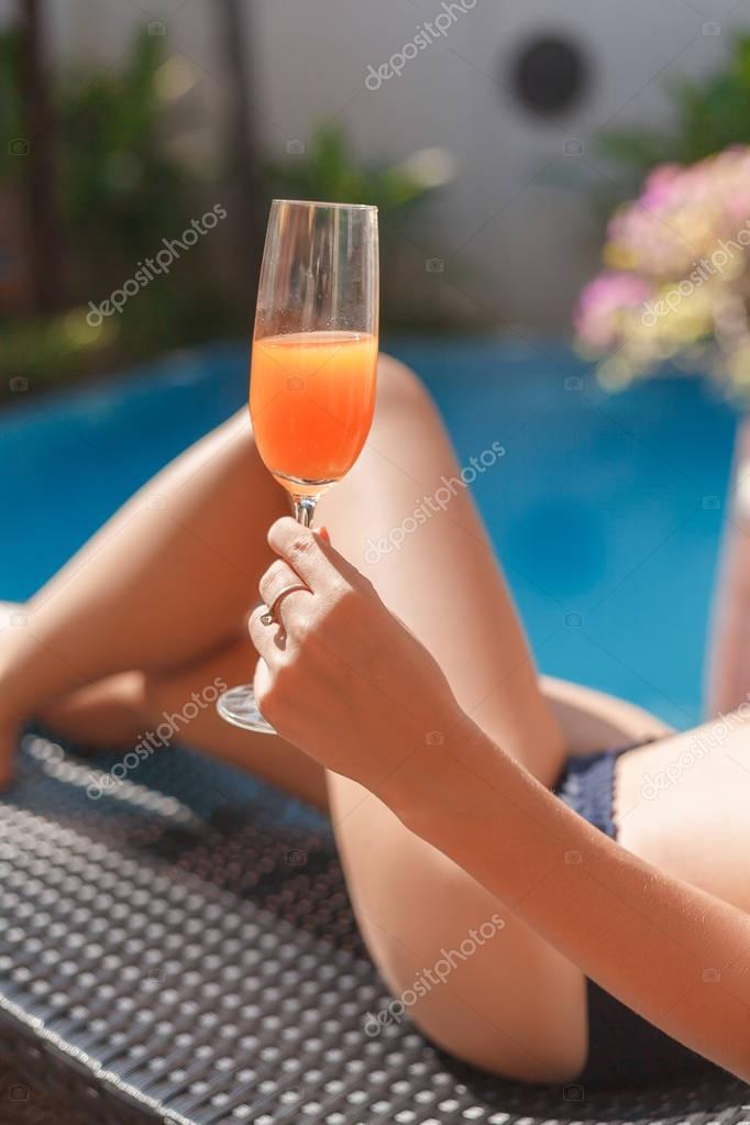 cropped shot of woman in bikini lying in sun lounge at poolside