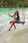 Fotografie beautiful girl on swing at tropical sea beach