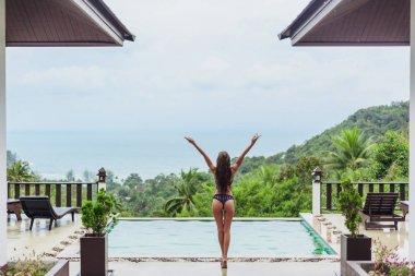 Rear view of girl in bikini at swimming pool on tropical resort stock vector