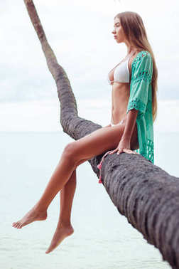 young attractive girl relaxing on palm tree over the ocean
