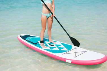 cropped view of woman on stand up paddle board on sea at tropical resort