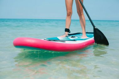 cropped view of woman on stand up paddle board on sea