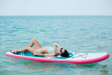young slim girl lying on paddle board on sea at tropical resort